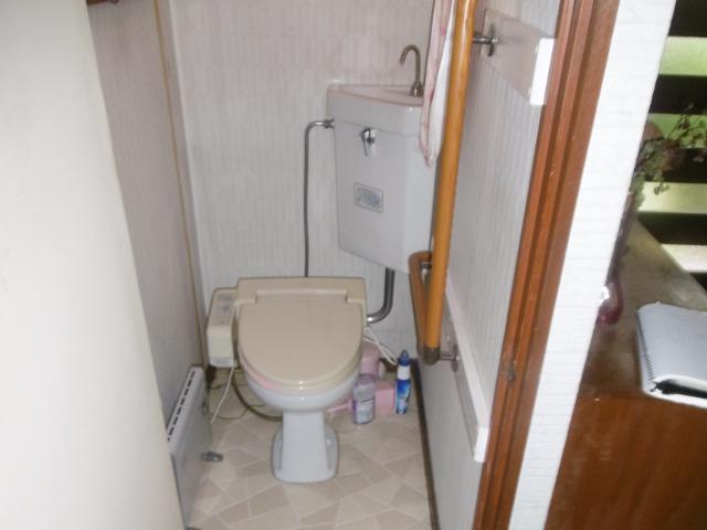 旧式のトイレでタンクの上の手洗いが奥の角にある